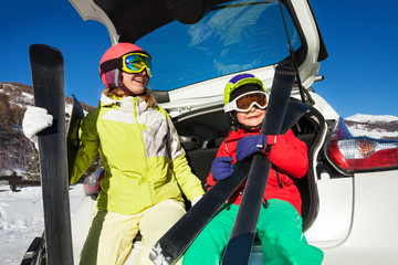 Happy skiers sitting in car trunk and holding skis