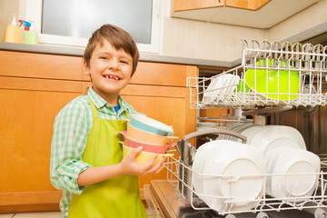 Smiling boy pulling out bowls of the dishwasher