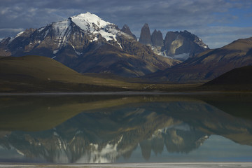 Peaks of Torres del Paine reflected in the still waters of Laguna Amarga in Torres del Paine National Park in southern Chile