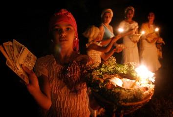 A young Romanian gypsy girl displays tarot cards during 'Sanziene' celebrations near Bucharest.