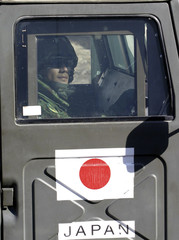Japanese soldier looks out from armoured vehicle during patrol in Samawa