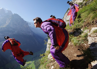 Base jumpers leap from a alpine cliff in the Lauterbrunnen valley in the Bernese Oberland, Switzerland