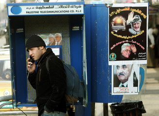 A Palestinian man uses public telephone decorated with posters of Mahmoud Abbas and Yasser Arafat in ...