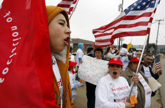 Villgas of Chihuahua, Mexico chants with other protesters as they march to the Dallas US Citizenship and Immigration Services office to protest delays in the processing of their applications