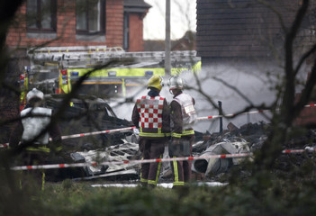 Fire crew stand in front of the wreckage of a light aircraft that crashed in a street in Farnborough