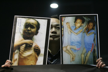 South Korean Christian Yoo Dae-sung holds photos of what he says are starving North Korean children at a rally in Seoul criticizing the infringement of human rights in North Korea