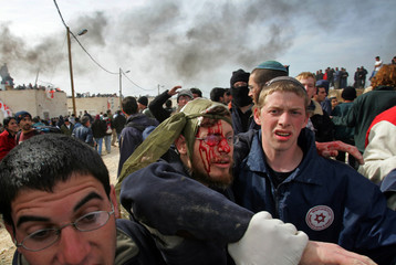 Injured Israeli ultranationalist protester is helped during clashes in Amona