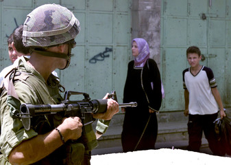AN ISRAELI SOLDIER POINTS HIS RIFLE AT A PALESTINIAN IN HEBRON.
