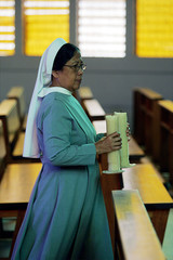 An Indonesian nun brings candles back inside the Santa Maria church after a Catholic mass was held f..