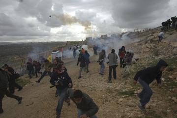 Palestinians avoid tear gas fired by Israeli border police in Bilin