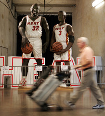 A media worker walks past statues of Miami Heat basketballers before their NBA Eastern Conference Finals Game 3 playoff match-up in Miami