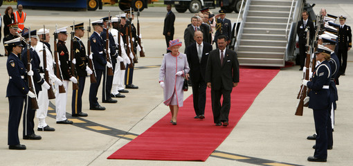 Britain's Queen Elizabeth II, Acting U.S. Chief of Protocol Raymond Martinez and Prince Philip pass an honor guard in Richmond