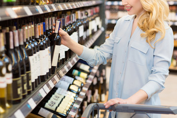 Attractive mature woman buying wine at the supermarket