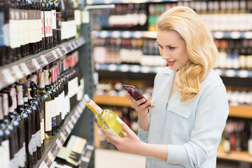 Woman using her smart phone at the wine supermarket