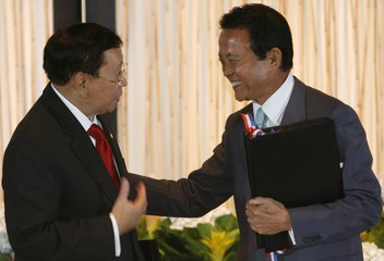 Japanese Foreign Minister Taro Aso laughs before exchanging documents with Philippine Foreign Minister Alberto Romulo (L) at the Philippine International Convention Center in Manila