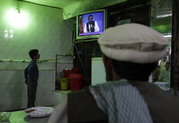 People watch the televised presidential debate in a restaurant in Kabul