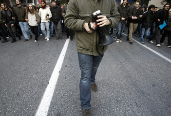 A protester holding a loudhailer leads a march through the streets of Athens