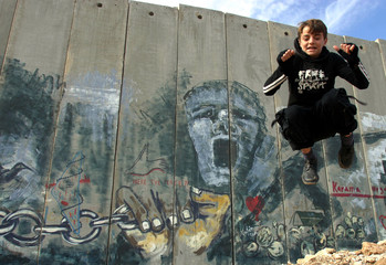 Palestinian boy plays in front of controversial Israeli barrier in West Bank town of Abu Dis on the edge of Jerusalem