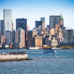 Statue ferry on its way to Liberty Island in front of New York skyline