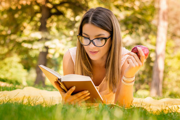outside portrait of young beautiful woman with apple reading book in park