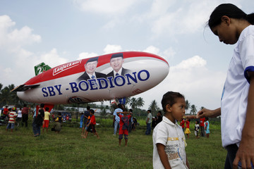 A mother feeds ice cream to her child near a balloon printed with pictures of Indonesia's President Yudhoyono and running mate Boediono, during campaign rally in Malang