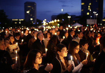 Participants hold candles during a commemorative ceremony on the occasion of the Shoah (Holocaust) Remembrance Day in Geneva