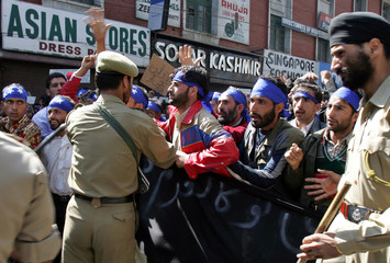 An Indian police officer stops activists from People's Conference, a Kashmiri separatist party, during a protest in Srinagar