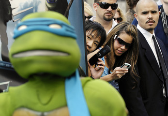 "Spectators on Hollywood Boulevard try to pictures of Teenage Mutant Ninja Turtles characters at the premiere of the animated film ""TMNT"" in Los Angeles"