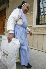 A nun carries humanitarian relief distributed by the Iraqi National Intelligence Service, at Mary's Daughters Church in Baghdad