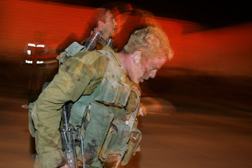 A wounded Israeli soldier walks into the Jewish Gaza Strip settlement of Kfar Darom in Gush Katif ...