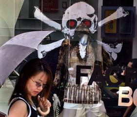 Woman walks past scull and crossbones fashion display in Harajuku, Tokyo.