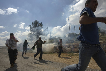 Protesters runr as a tear gas lands near them during a protest against Israel's security barrier in the West Bank village of Bilin