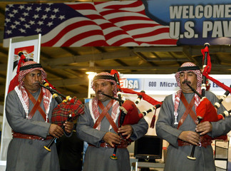 BEDOUIN GUARDS PLAY BAGPIPES TO WELCOME U.S. OFFICIALS TO TRADE FAIR IN AMMAN.