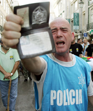 A policeman displays his badge during a demonstration in Lisbon.