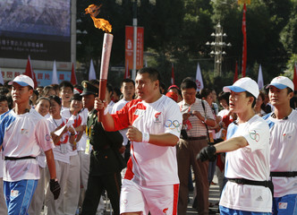 Chinese boxer Abdul Xukur is surrounded by security guards as he carries the Olympic Torch for the Xinjiang leg of the Olympic torch relay at the Peoples Square in Urumqi