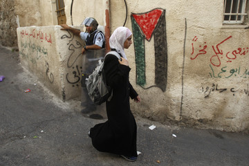 A Palestinian youth walks past an Israeli police officer in East Jerusalem