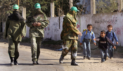 Palestinian school boys run to shake hands with masked Hamas militants in Southern Gaza Strip