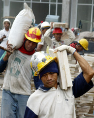 Indonesian workers carry tools and building materials at a construction site in Jakarta.