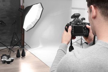 Young professional photographer with camera in studio