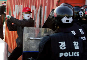 A student protestor clashes with riot police during the Asia-Pacific Economic Cooperation (APEC) Summit in Pusan