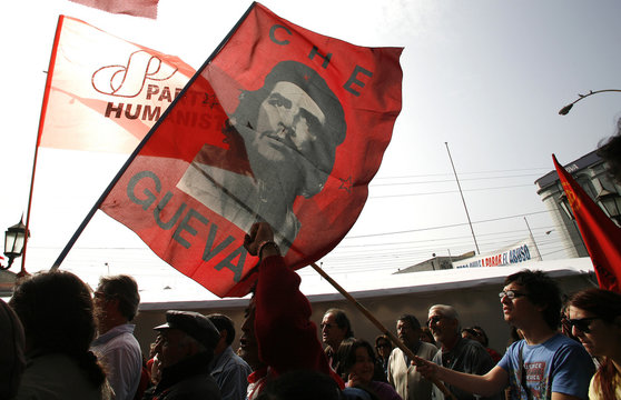 Demonstrators with a flag of  Argentine revolutionary icon Ernesto Che Guevara takes part during May Day rallies in Valparaiso city.