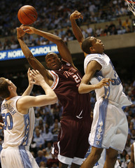Virginia Tech'a Witcher battles for rebound with University of North Carolina's Hansbrough and Wright during NCAA basketball game in Chapel Hill