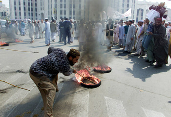 ISLAMIC RELIGIOUS STUDENTS BURN TYRES DURING ANTI-U.S. RALLY IN LAHORE.