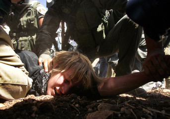 Israeli troops arrest a demonstrator during a protest in West Bank village of Bilin.