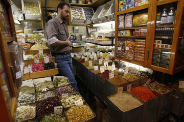 Shop owner inspects the herbs and spices for sale at his shop in Bab Touma in the Old City of Damascus