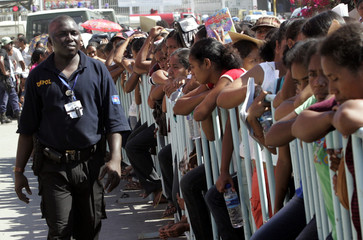 A U.N. policeman keeps order as thousands of young East Timorese queue to apply for jobs in Dili