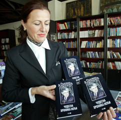 A woman displays a book of Radovan Karadzic, former Bosnian Serb leader [wanted by the United Nation..