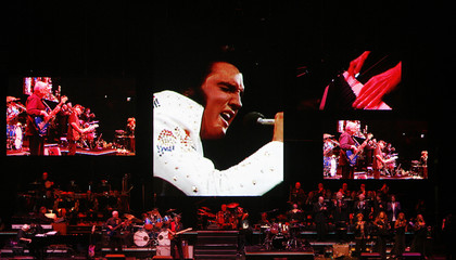A live band backs up a virtual Elvis during a memorial concert of Elvis footage in Memphis, Tennessee