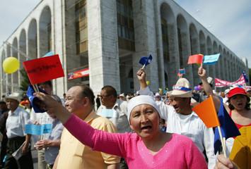 Demonstrators wave flags during opposition protest in Bishkek