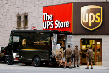 United Parcel Service drivers wait to load UPS truck outside store in Los Angeles